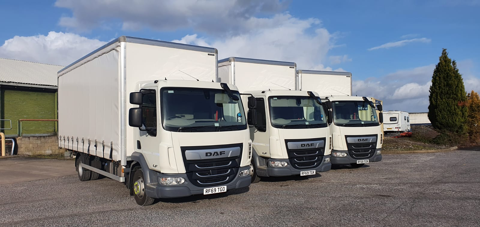 A row of three white DAF LF 7.5t vehicles in a yard